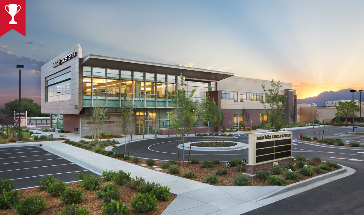 External photo of Jordan Valley Cancer Center at sunrise. View of building with parking lot in front and sun peaking over mountains in the distance. Designed by TSA Architects.