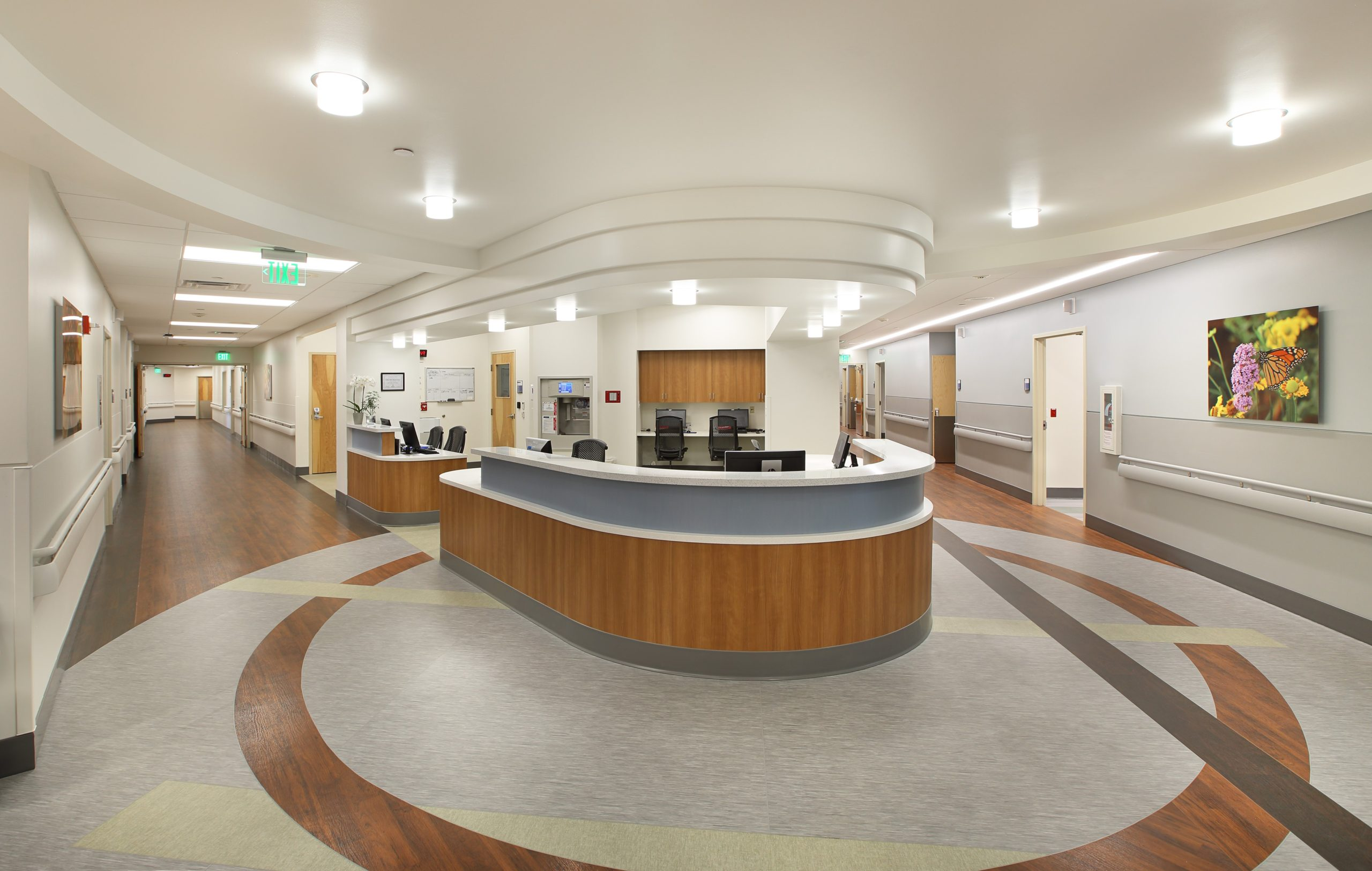 Nurses main desk with halls on both sides to patient rooms. Recently remodeled clean, bright station. View from the left side. Designed by TSA Architects.