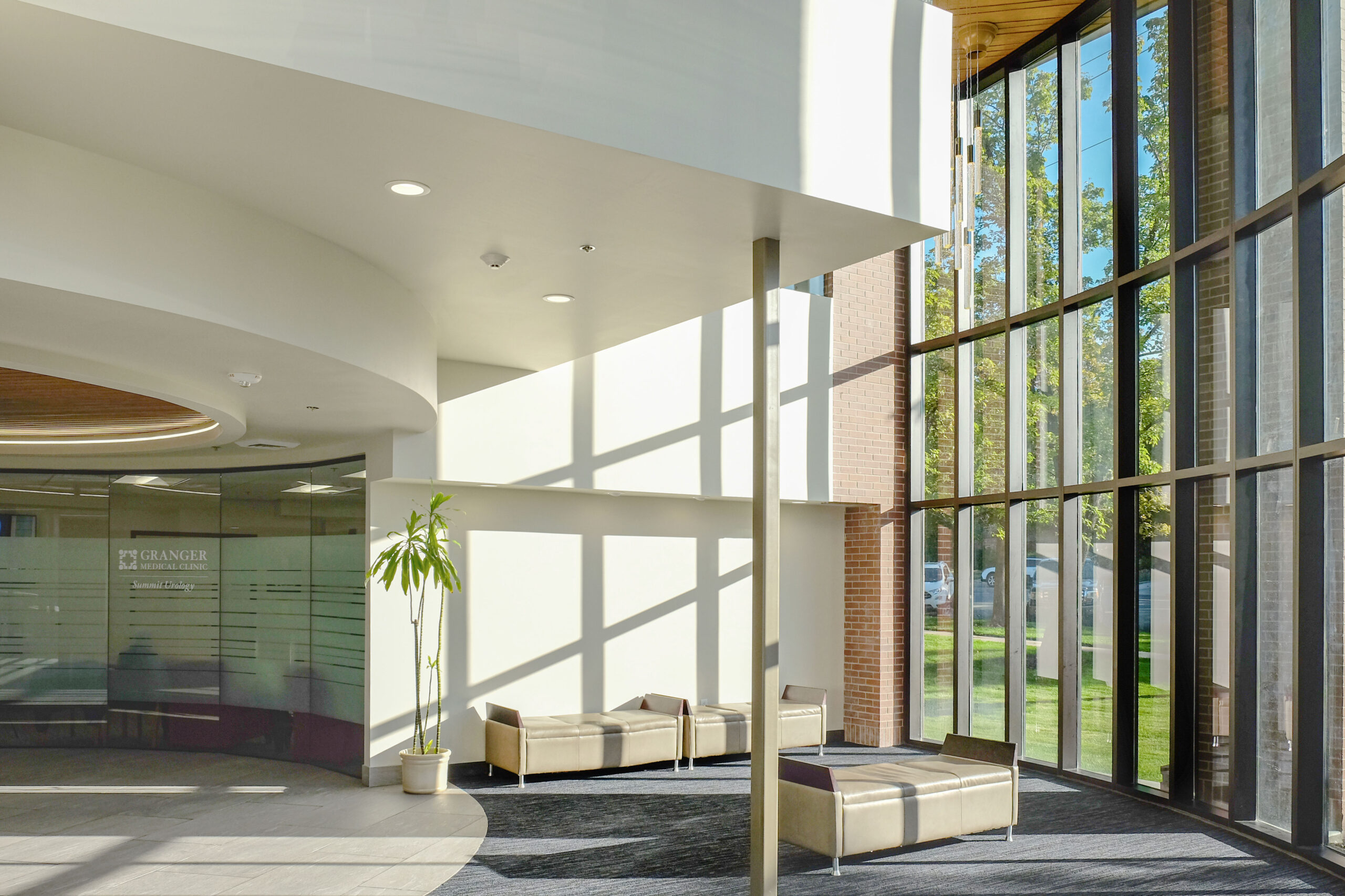 Medical office building design showing two-story atrium with natural light over sitting area near elevators.