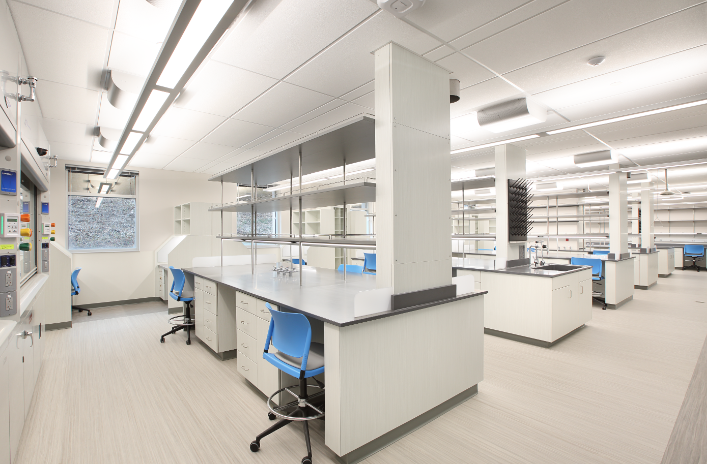 This University Lab design shows 5 rows of clean white lab desks with 2 blue chairs at each station. There are also shelves above the desks that don't have a back on them so you can see through. It gives you more surface space but still keep the room open and bright.